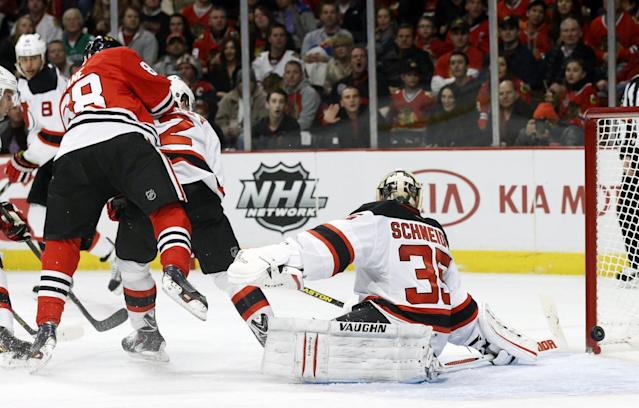 Chicago Blackhawks right wing Patrick Kane, left, scores past New Jersey Devils goalie Cory Schneider (35) during the second period of an NHL hockey game Monday, Dec. 23, 2013, in Chicago. (AP Photo/Charles Rex Arbogast)