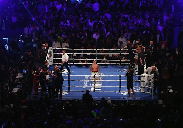 Triumph - Ukrainian boxer Oleksandr Usyk (C) kneels on the canvas after the 12th round of his unanimous points world heavyweight title win over Anthony Joshua (AFP/Adrian DENNIS)