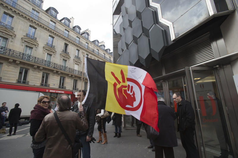 A supporter of the Indian cause, holds a flag of the American Indian Movement, stands outside of the Druout's auction house to protest the auction of Native American Hopi tribe masks in Paris, Friday, April 12, 2013. A contested auction of dozens of Native American tribal masks went ahead Friday afternoon following a Paris court ruling, in spite of appeals for a delay by the Hopi tribe, its supporters including actor Robert Redford, and the U.S. government. (AP Photo/Michel Euler)