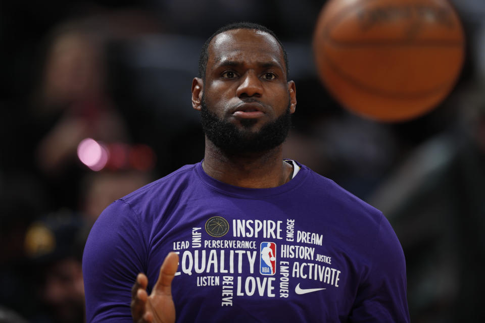 """LeBron James, in a purple shirt with sayings such as """"inspire, equality, love, activate"""" prepares to catch a basketball."""