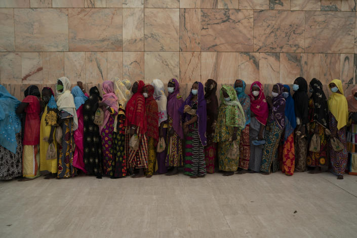 Wearing protective masks, women stand in line to enter the Grand Mosque of Touba as they take part in the celebrations of the Grand Magal of Touba, Senegal, Monday, Oct. 5, 2020. Despite the coronavirus pandemic, thousands of people from the Mouride Brotherhood, an order of Sufi Islam, are gathering for the annual religious pilgrimage to celebrate the life and teachings of Cheikh Amadou Bamba, the founder of the brotherhood. (AP Photo/Leo Correa)