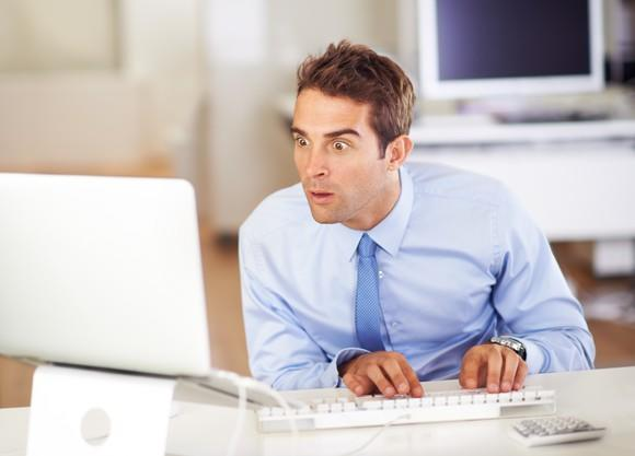 A man with eyes open wide looks at a computer monitor.