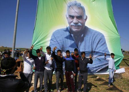 Kurdish men pose for a picture in front of the portrait of jailed Kurdish militant leader Abdullah Ocalan of the Kurdistan Workers Party (PKK) during a gathering celebrating Newroz in Turkey
