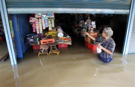 A resident walks outside a flooded shop at Srimahaphot district in Prachin Buri province, east of Bangkok September 24, 2013. REUTERS/Chaiwat Subprasom