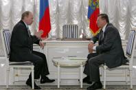 FILE PHOTO: Russian President Putin and Prime Minister Zubkov talk at Vnukovo II airport in Moscow