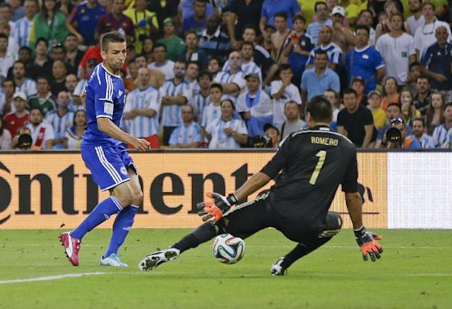 Bosnia's Vedad Ibisevic, left, kicks the ball past Argentina's goalkeeper Sergio Romero (1) to score his side's first goal during the group F World Cup soccer match between Argentina and Bosnia at the Maracana Stadium in Rio de Janeiro, Brazil, Sunday, June 15, 2014. (AP Photo/Kirsty Wigglesworth)