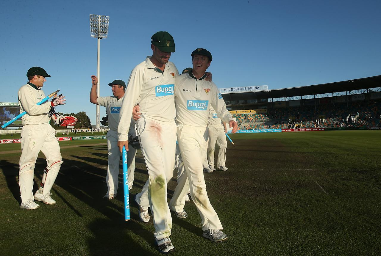 HOBART, AUSTRALIA - MARCH 26:  George Bailey and Alex Doolan of the Tigers celebrate victory in the Sheffield Shield final between the Tasmania Tigers and the Queensland Bulls at Blundstone Arena on March 26, 2013 in Hobart, Australia.  (Photo by Mark Metcalfe/Getty Images)