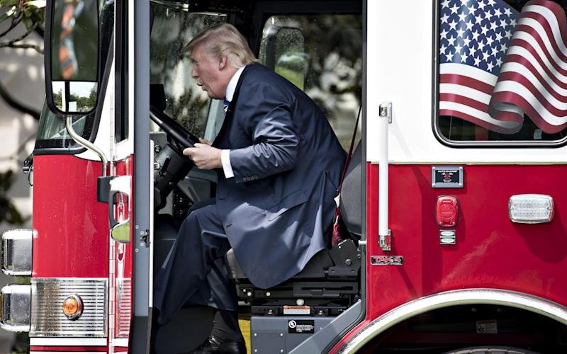 U.S. President Donald Trump sits in a fire truck while participating in a Made in America event - Credit: Bloomberg