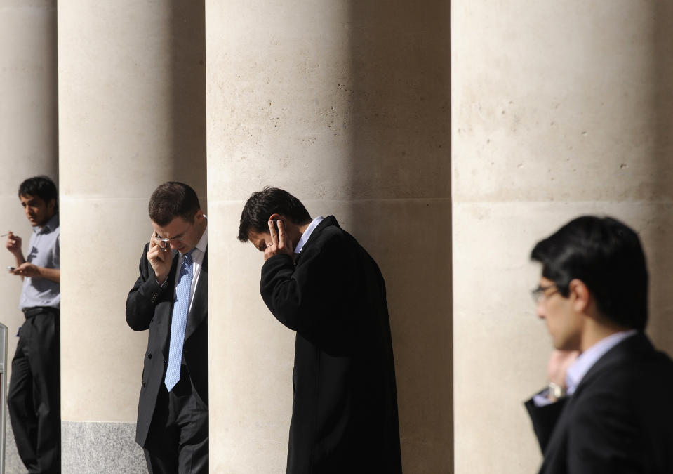 City workers make phone calls outside the London Stock Exchange in Paternoster Square in the City of London at lunchtime October 1, 2008. European policymakers have called on the U.S. Senate to approve a revised rescue plan aimed at tackling the worst financial crisis since the 1930s. REUTERS/Toby Melville (BRITAIN)