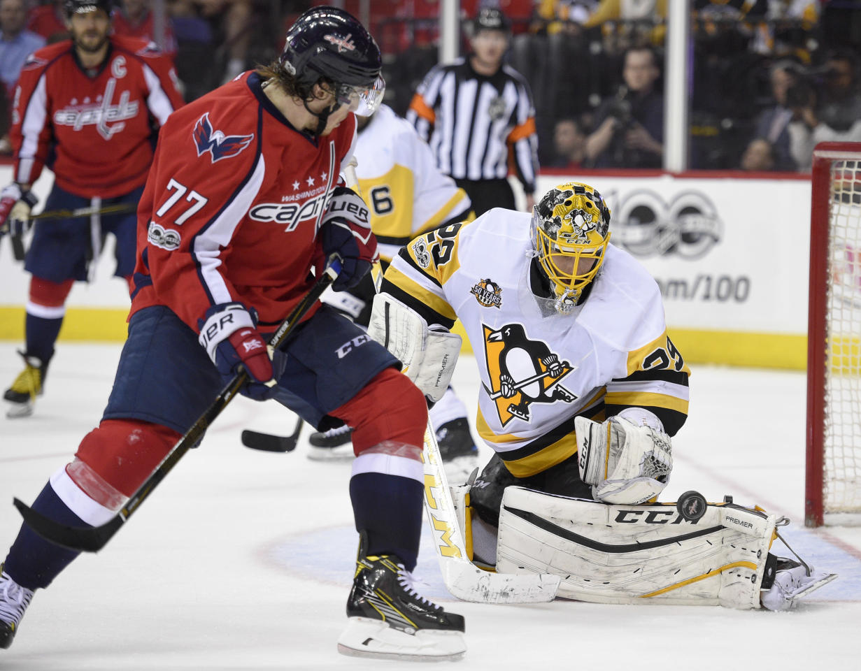 Pittsburgh Penguins goalie Marc-Andre Fleury (29) watches the puck bounce in front of Washington Capitals right wing T.J. Oshie (77) during the second period of Game 1 in an NHL hockey Stanley Cup second-round playoff series, Thursday, April 27, 2017, in Washington. (AP Photo/Nick Wass)