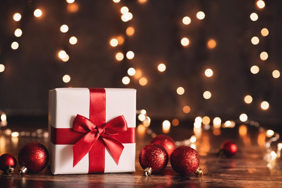 Red Christmas gift box and baubles on background of defocused golden lights