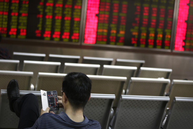 A man checks stock prices through his smartphone at a brokerage house in Beijing, Wednesday, April 24, 2019. Shares were mostly lower in Asia on Wednesday despite the S&P 500's all-time record high close the day before.(AP Photo/Andy Wong)