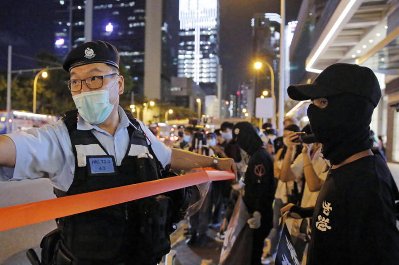 Police officers put up a cordon line in front of the protesters during a protest in Hong Kong. A report from an official Hong Kong police watchdog says officers used force only in response to threats to their safety. (AP Photo/Kin Cheung)