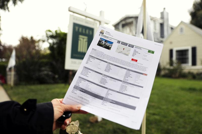 FILE PHOTO -- A woman holds a piece of paper advertising a home for sale in Santa Monica