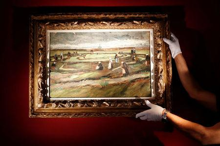 """Artcurial's employee poses as he holds the painting """"Raccommodeuses de filets dans les dunes, 1882"""" (Women Mending Nets in the Dunes) by painter Vincent Van Gogh during a preview for media at Artcurial Auction House in Paris"""