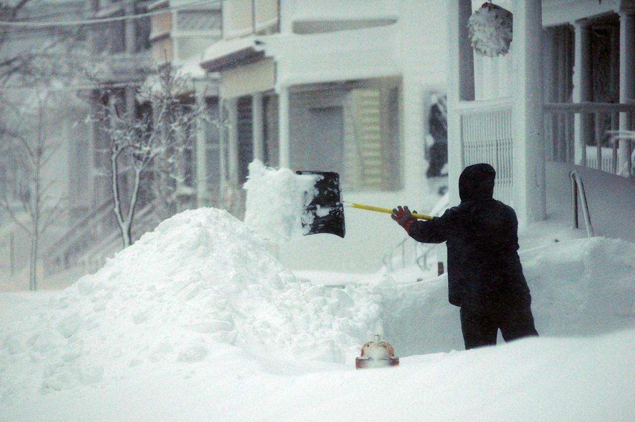 WINTHROP, MA - FEBRUARY 9: A man shovels snow on Cutler Street February 9, 2013 in Winthrop, Massachusetts.  The powerful storm has knocked out power to 650,000 and dumped more than two feet of snow in parts of New England.  (Photo by Darren McCollester/Getty Images)