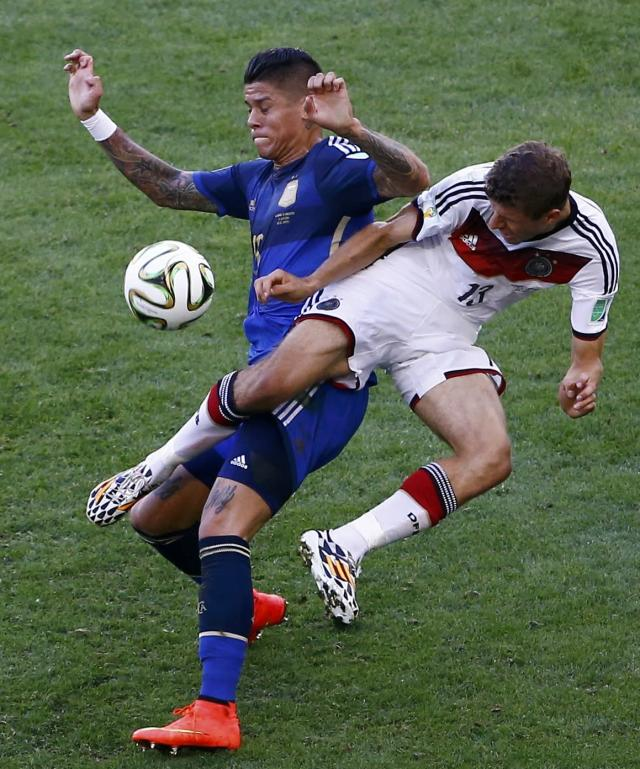 Germany's Thomas Muelle (R) fights for the ball with Argentina's Marcos Rojo during their 2014 World Cup final at the Maracana stadium in Rio de Janeiro July 13, 2014. REUTERS/Leonhard Foeger (BRAZIL - Tags: SOCCER SPORT WORLD CUP)