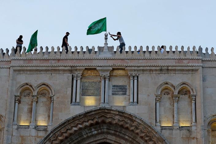 Palestinians place the Hamas movement flag atop al-Aqsa mosque in Jerusalem's Old City on May 10, 2021, ahead of a planned march to commemorate Israel's takeover of Jerusalem in the 1967 Six-Day War.
