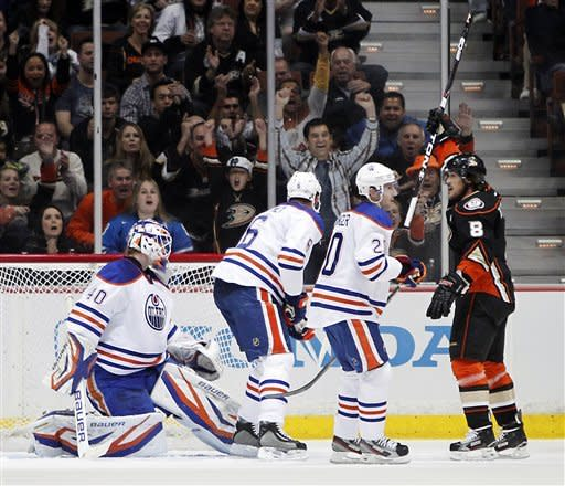 Anaheim Ducks right wing Teemu Selanne, right, holds his stick up after scoring a goal against Edmonton Oilers goalie Devan Dubnyk in the first period of an NHL hockey game in Anaheim, Calif., Sunday, April 1, 2012. (AP Photo/Christine Cotter)