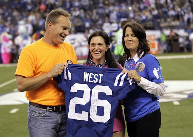 Indianapolis Colts vice chair/owner Carlie Irsay-Gordon, center, presents a jersey to Scott West, left, and his wife Julie West, right, during halftime of an NFL football game between the Colts and the Seattle Seahawks in Indianapolis, Sunday, Oct. 6, 2013. The West's son Jake West, a 17-year-old LaPorte High School student, collapsed during football practice and later died of an enlarged heart on Sept. 25. (AP Photo/AJ Mast)