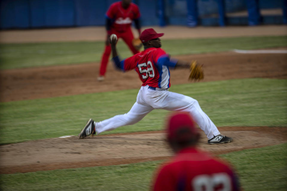 Cuba's pitcher Yoanni Yera Montalvo throws the ball during a training session at the Estadio Latinoamericano in Havana, Cuba, Tuesday, May 18, 2021. A little over a week after the start of the Las Americas Baseball Pre-Olympic in Florida, the Cuban team does not have visas to travel to the United States. (AP Photo/Ramon Espinosa)
