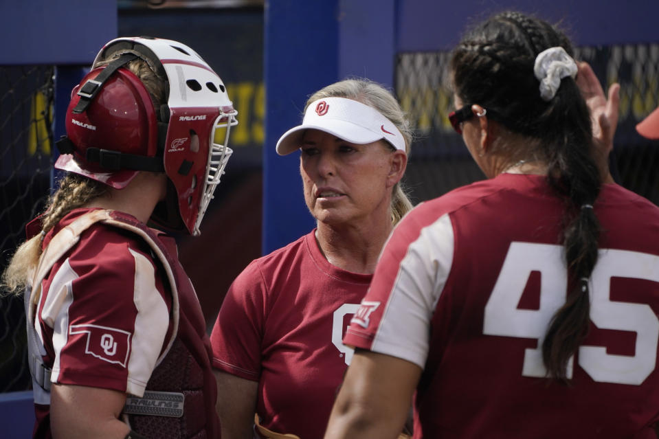 Oklahoma coach Patty Gasso, center, talks with catcher Lynnsie Elam, left and pitcher Giselle Juarez (45) during the team's NCAA Women's College World Series softball game against James Madison, Monday, June 7, 2021, in Oklahoma City. Gasso has been one of the most outspoken coaches regarding differences in scheduling and the quality of the facilities between the Women's College World Series and the men's baseball College World Series. (AP Photo/Sue Ogrocki)