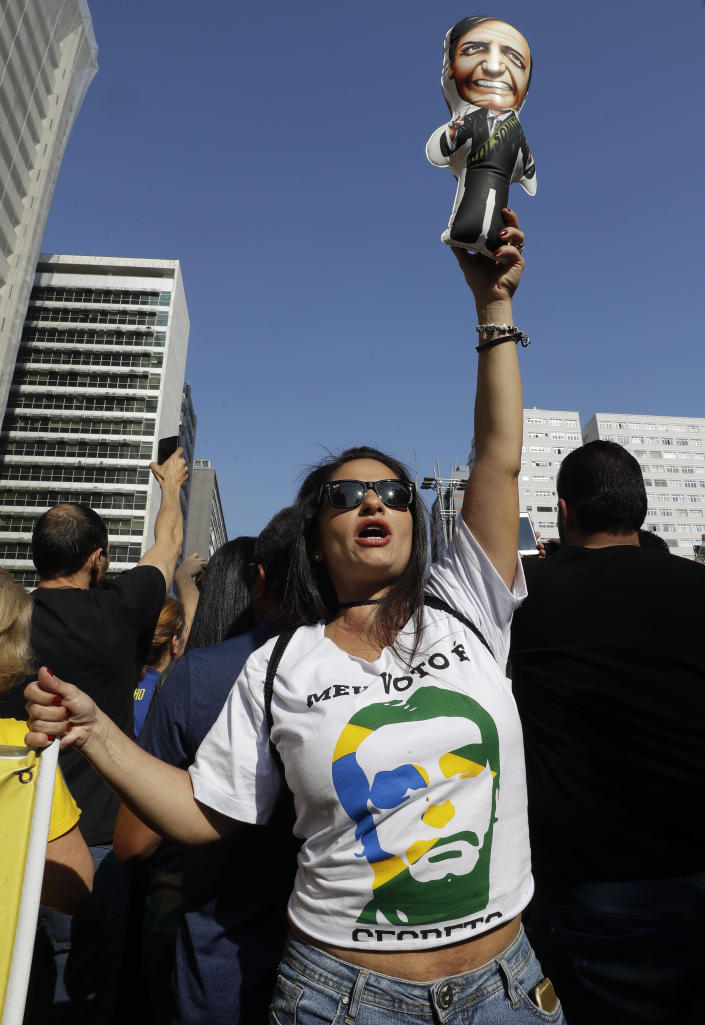 A supporter of Jair Bolsonaro, presidential candidate for the National Social Liberal Party who was stabbed during a campaign event days ago, holds up a doll in his image during a march along Paulista Avenue to show support for him in Sao Paulo, Brazil, Sunday, Sept. 9, 2018. Brazil will hold general elections on Oct. 7. (AP Photo/Andre Penner)
