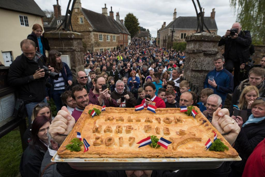 <p>Hallaton hosts the Hare Pie Scramble and Bottle Kicking events. The Bottle Kicking follows the Hare Pie Scramble, two events that are combined to form an ancient custom that dates back to the early eighteenth century, and one of the oldest in British History. The first part consists of a blessing of a Hare Pie by a local vicar, before it is cut up and thrown to the crowd, who 'scramble' to get a piece, believing it will bring good luck. The second part, the Bottle kicking sees two rival villages, Hallaton, and neighboring Medbourne attempt to carry a 'bottle' which is actually a keg of beer, from the Hare Pie Bank, and get it across a boundary stream for their own village. (Dan Kitwood/Getty Images) </p>