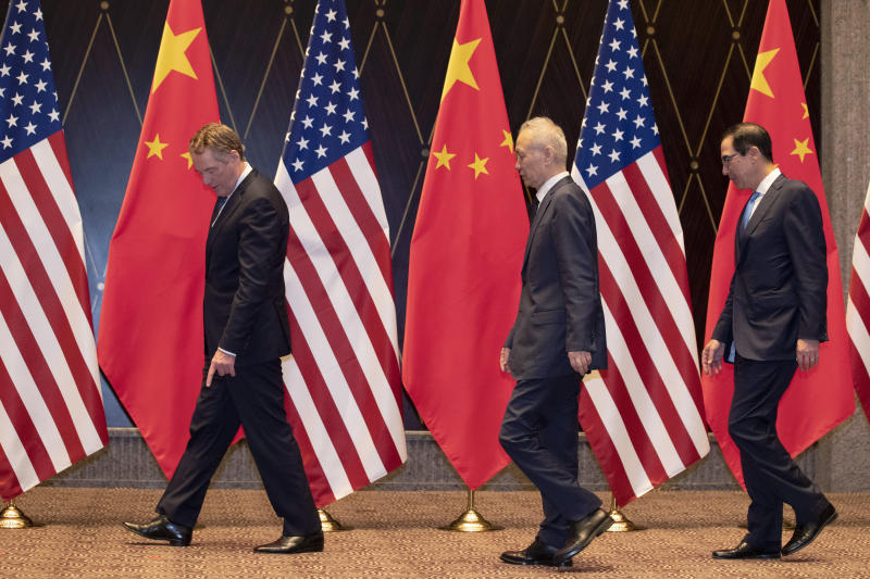 U.S. Trade Representative Robert Lighthizer, left, points at markers on the floor as he leads Chinese Vice Premier Liu, center, and Treasury Secretary Steven Mnuchin, right, to their position for a family photo at the Xijiao Conference Center in Shanghai on Wednesday, July 31, 2019. (AP Photo/Ng Han Guan, Pool)