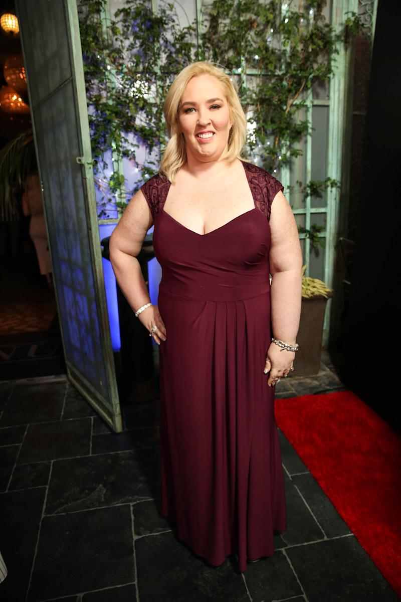 Mama June Shannon poses with her hand on her hip wearing a red gown
