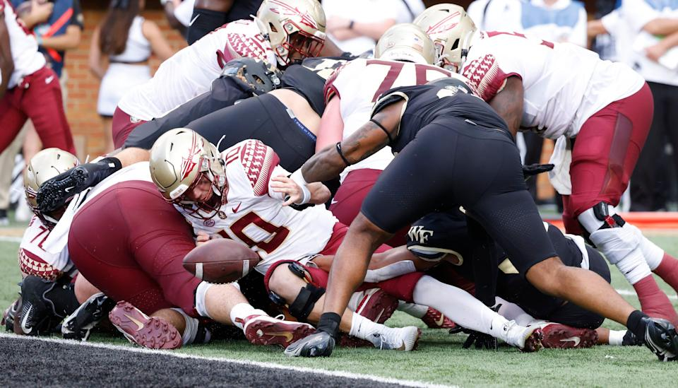 Wake Forest linebackers Joshua Sosanya (32) and DJ Taylor (top, right) strip the ball from Florida State quarterback McKenzie Milton (10) near the goal line.