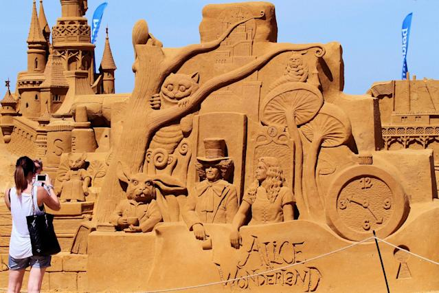 "<p>An attendee takes a photo of a sculpture during the Sand Sculpture Festival ""Disney Sand Magic"" in Ostend, Belgium. (Photo courtesy of Disneyland Paris) </p>"