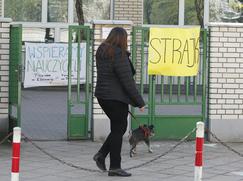A woman walks by a school where teachers are taking part in nationwide pay strike, with banners declaring the participation in the strike and also parent's support for it, in Warsaw, Poland, Monday, April 15, 2019. The right-wing government says it has money only to grant half of the teachers' demands in a sign that its policy of pre-election spending has reached its limit.(AP Photo/Czarek Sokolowski)