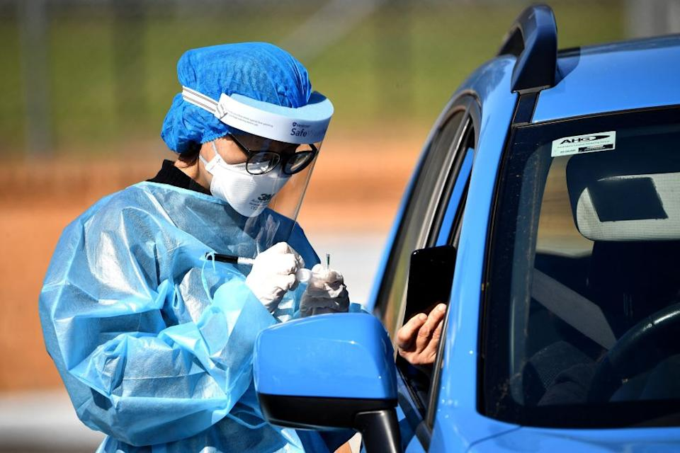 A health worker takes a swab sample at a Covid-19 coronavirus drive through testing site in the Smithfield suburb of Sydney.