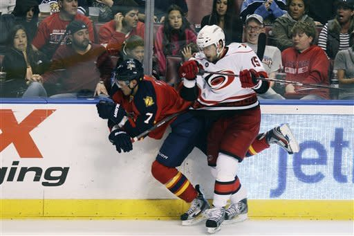 Florida Panthers' Dmitry Kulikov (7) falls to the ice after slamming into Carolina Hurricanes' Tuomo Ruutu (15) during the second period of a NHL hockey game in Sunrise, Fla., Saturday, April 7, 2012. (AP Photo/J Pat Carter)