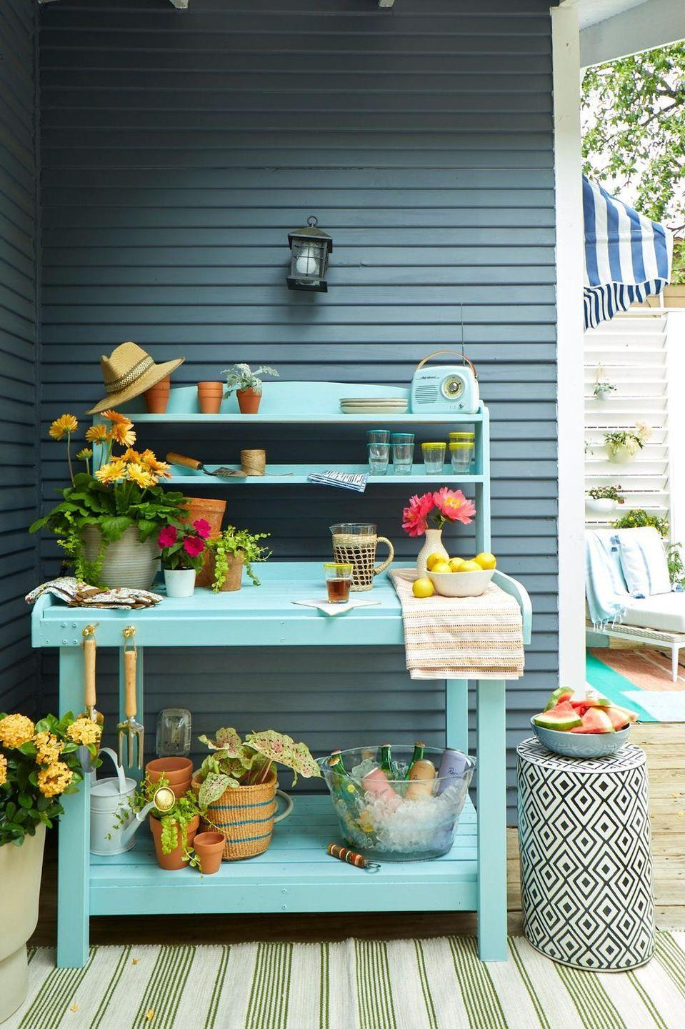 <p>Bring a wooden work bench outside, give it a coat of fresh paint, and then use it for, well, everything. When you're entertaining, turn it into a bar cart or serving station. Otherwise, let it become your catch-all spot for gardening tools, empty pots, and watering cans. </p>