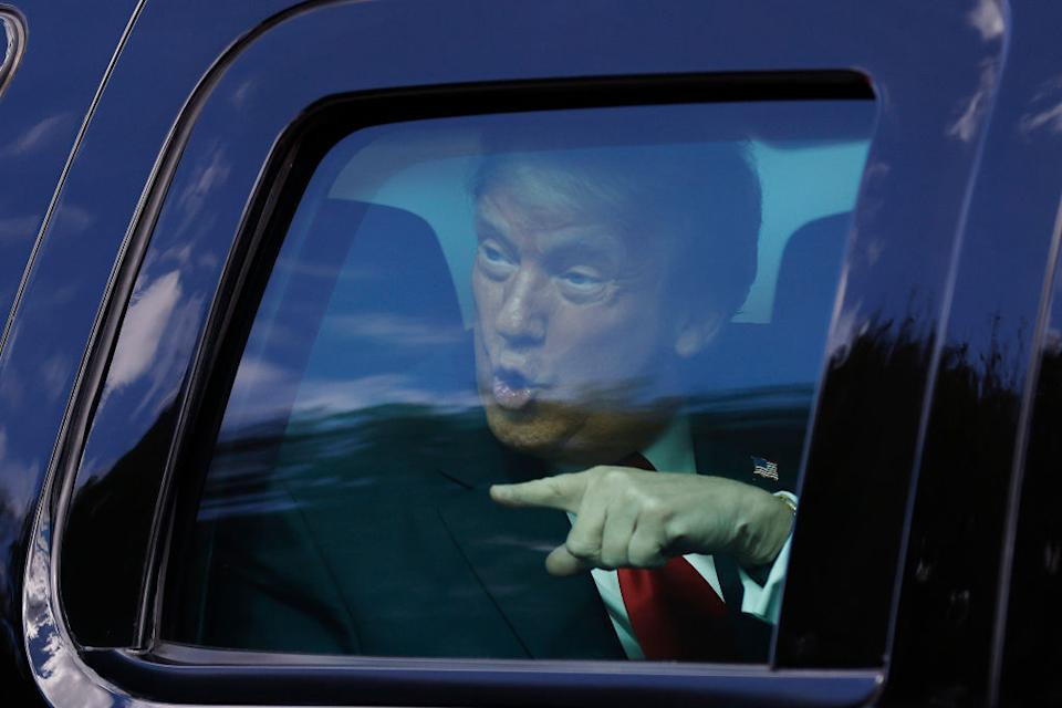 Outgoing US President Donald Trump waves to supporters lined along on the route to his Mar-a-Lago estate in West Palm Beach, Florida.