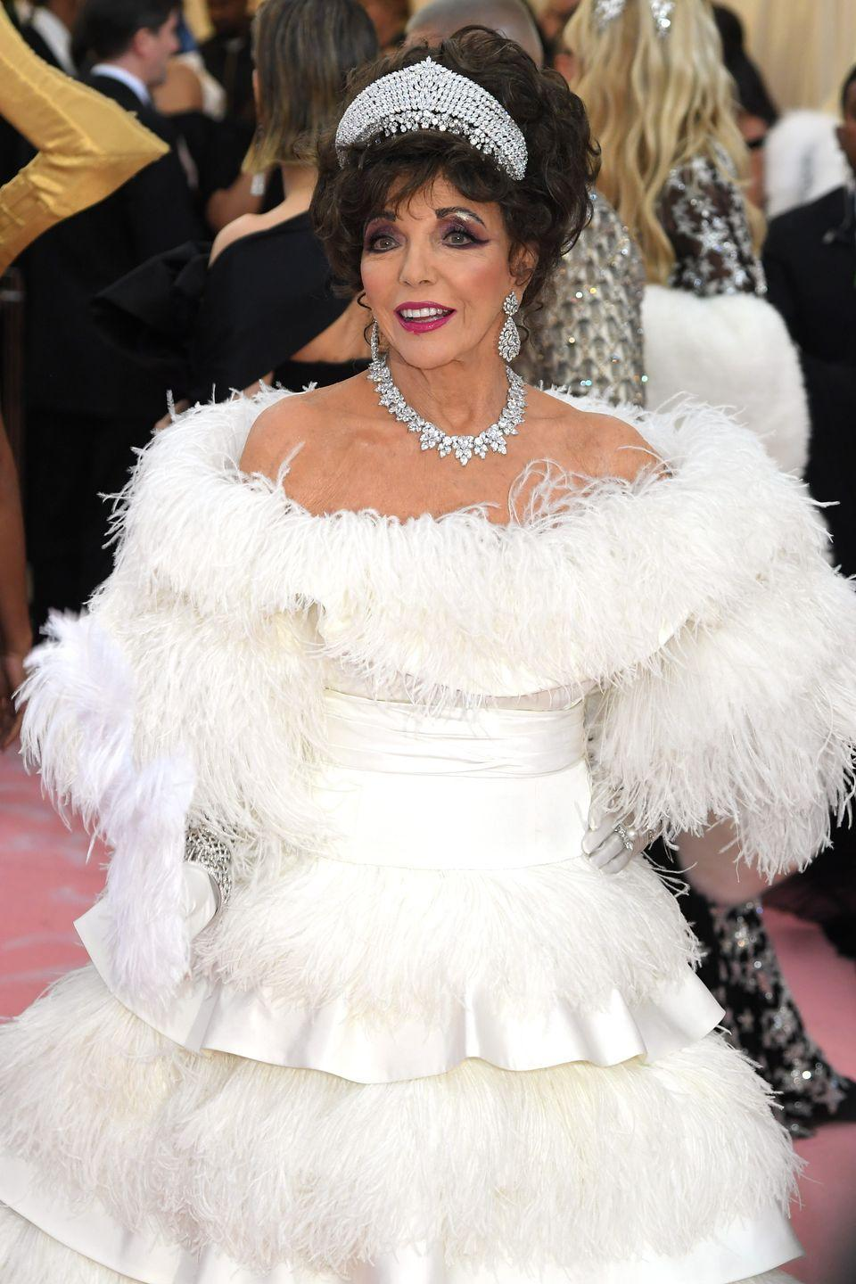 <p>Taking the theme of 'Camp' in her immaculately shod stride, Collins went to the 2019 Met Gala dressed as her own Dynasty character, Alexis Carrington. She paired her feathered Valentino couture gown with a sparkling suite of diamond jewellery, including an impressive kokoshnik tiara.</p>
