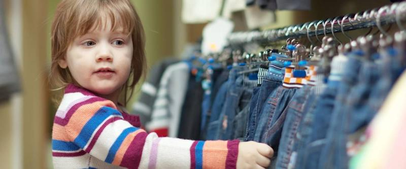 2 years child chooses jeans at clothes shop