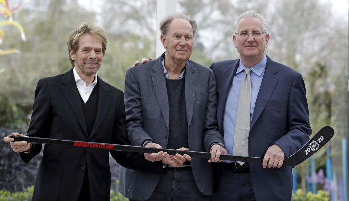 FILE - In this April 11, 2018, file photo, part-owners Jerry Bruckheimer, from left, and David Bonderman pose with Tod Leiweke and a hockey stick during a news conference naming Leiweke as the president and CEO for a prospective NHL expansion team, in Seattle. The NHL Board of Governors is meeting to give final approval to Seattle's bid to add the league's 32nd team. Play would be expected to begin in the 2021-22 season. (AP Photo/Elaine Thompson, File)