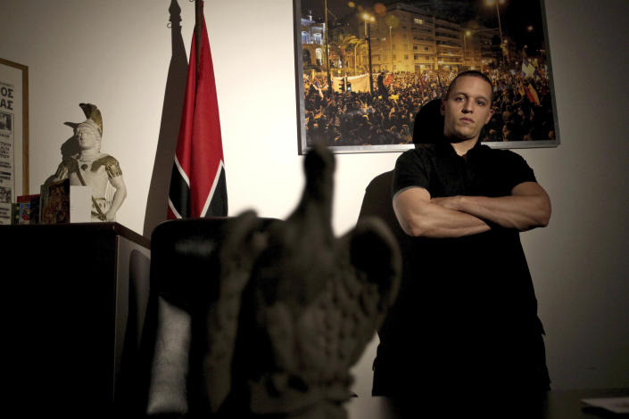 FILE - In this April 25, 2012 file photo, extreme right Golden Dawn party spokesman Ilias Kassidiaris poses next to the party flag and a statue of Alexander the Great, at the party headquarters in Athens. Kassidiaris was arrested Saturday, Sept. 28, 2013, on charges of forming a criminal organization. Greek police also confirmed the arrest of the party leader Nikos Mihaloliakos on the same charges. (AP Photo/Petros Giannakouris, File)