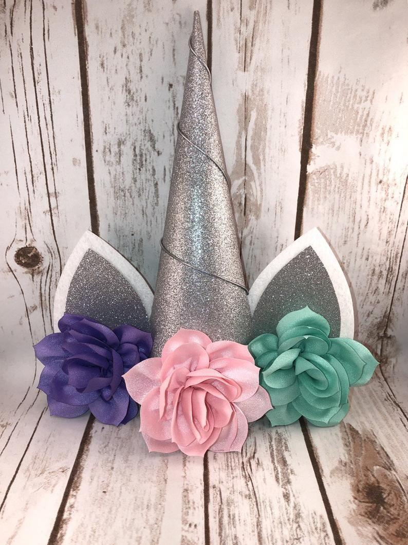 """<p><strong>BellaBowtiqueDesigns</strong></p><p>etsy.com</p><p><strong>$20.00</strong></p><p><a href=""""https://go.redirectingat.com?id=74968X1596630&url=https%3A%2F%2Fwww.etsy.com%2Flisting%2F646842448%2Ftree-topper-unicorn-tree-topper&sref=https%3A%2F%2Fwww.goodhousekeeping.com%2Fholidays%2Fchristmas-ideas%2Fg2721%2Fchristmas-tree-toppers%2F"""" rel=""""nofollow noopener"""" target=""""_blank"""" data-ylk=""""slk:Shop Now"""" class=""""link rapid-noclick-resp"""">Shop Now</a></p><p>A unicorn tree topper isn't the traditional choice for a family Christmas tree but it would look adorable paired with that <a href=""""https://www.goodhousekeeping.com/holidays/christmas-ideas/a25412271/easy-diy-christmas-ornaments/"""" rel=""""nofollow noopener"""" target=""""_blank"""" data-ylk=""""slk:DIY ornament"""" class=""""link rapid-noclick-resp"""">DIY ornament</a> the little one made.</p>"""