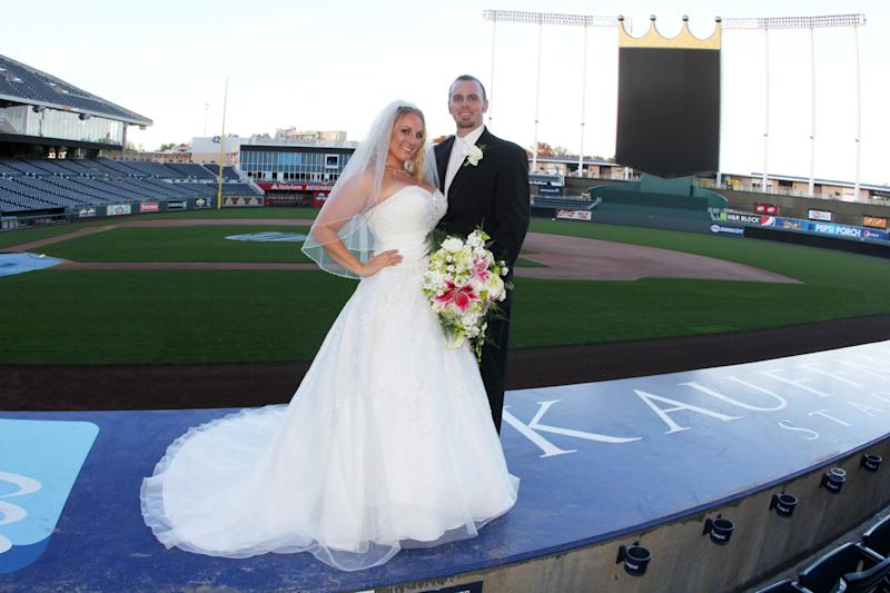 "This Oct. 20, 2012 photo released by Ashley Crank shows her posing with her husband Cody Crank during their wedding at Kauffman Field in Kansas City. Some couples, find that the massive stadiums where they enjoy hearing the crack of the bat can also be the perfect place to hear their beloved say, ""I do."" (AP Photo/Jessica Thomas)"