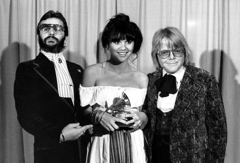 """FILE - This Feb. 20, 1977 file photo shows singer Linda Ronstadt is flanked by Ringo Starr, left, and Paul Williams after she was named best pop singer for her """"Hasten Down the Wind"""" at The 19th Annual Grammy Awards in Los Angeles. A documentary, """"Linda Ronstadt: The Sound of My Voice,"""" will premiere on CNN on New Year's Day.  (AP Photo)"""