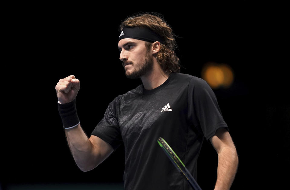 Greece's Stefanos Tsitsipas celebrates winning a point against Austria's Dominic Thiem, during their London 2020 group singles match on day one of the ATP Finals tennis championship at the O2 Arena, London, Sunday Nov. 15, 2020. (John Walton/PA via AP)