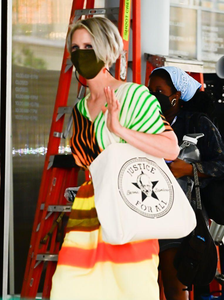 """<p>Nixon aka Miranda Hobbes was spotted on set in a colourful Dries Van Noten dress (now reduced, online) accessorised with a tote bag emblazoned with a picture of Bernie Sanders and the text 'Justice For All'. Very fitting for the woman who, in real life, ran for New York City mayor. </p><p><a class=""""link rapid-noclick-resp"""" href=""""https://www.net-a-porter.com/en-gb/shop/product/dries-van-noten/dorias-drawstring-tie-dyed-striped-faille-midi-dress/1316836"""" rel=""""nofollow noopener"""" target=""""_blank"""" data-ylk=""""slk:SHOP NOW"""">SHOP NOW</a> Dries Van Noten Dorias dress, £47.50</p>"""