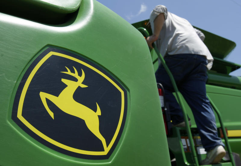 FILE - In this photo July 29, 2010 file photo, a farmer climbs aboard a John Deere 9770 STS combine near Coy, Ark.  Deere & Co. is expected to report quarterly results Wednesday, May 15, 2013. (AP Photo/Danny Johnston, File)