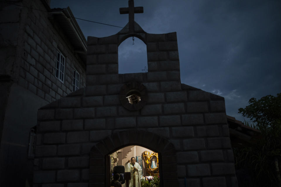 Friar Leopoldo Serrano celebrates Mass, broadcast via Facebook, at a chapel in Mission San Francisco de Asis, Honduras, late Saturday, June 19, 2021. Located on the border of the departments of Santa Barbara and Copan, his sprawling mission straddles the road that is one of the region's main drug trafficking corridors. (AP Photo/Rodrigo Abd)