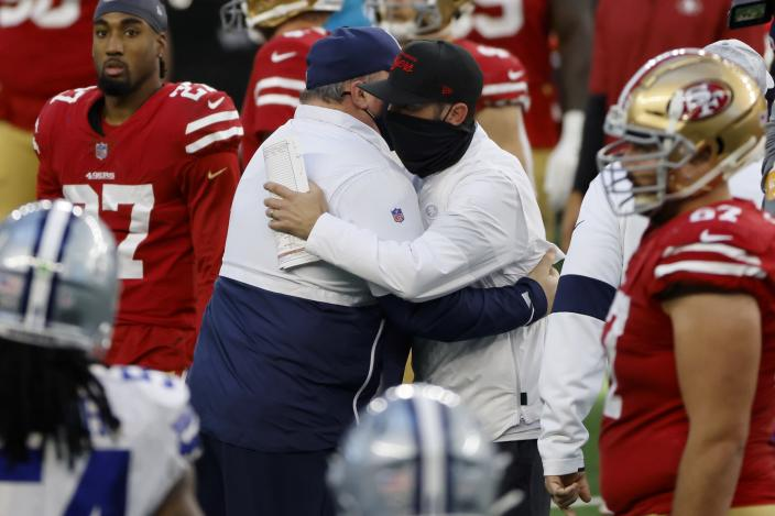 Dallas Cowboys head coach Mike McCarthy, center left, and San Francisco 49ers head coach Kyle Shanahan, center right, greet each other after their NFL football game in Arlington, Texas, Sunday, Dec. 20, 2020. (AP Photo/Ron Jenkins)