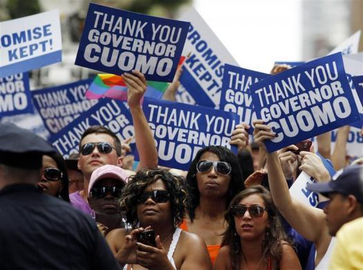 People lining the parade route hold signs thanking New York Governor Andrew Cuomo for the legalization of gay marriage during the Gay Pride Parade in New York June 26, 2011.